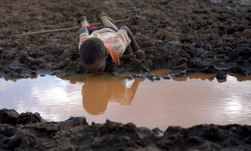 A boy drinks water from a pond in Bule Duba village in the outskirts of Moyale, near the edge of Oroma and Somali regions of Ethiopia